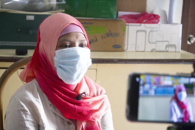 Raisa keenly listens to the health advice of the health worker at the rural health unit.
